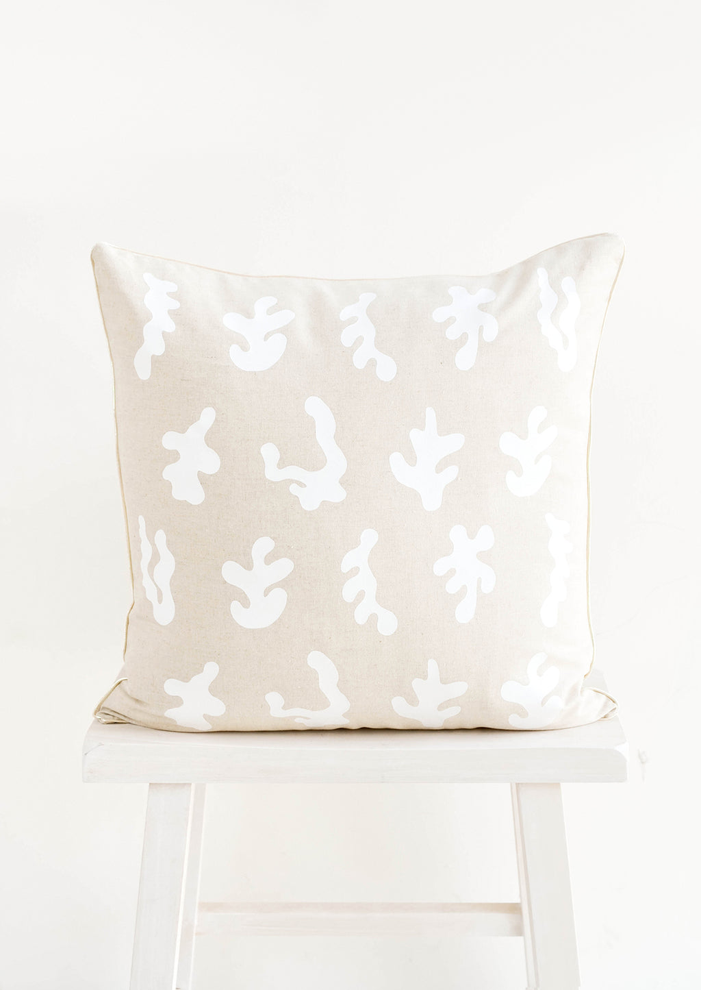 1: Square throw pillow in natural linen color with white, screen printed seaweed shapes