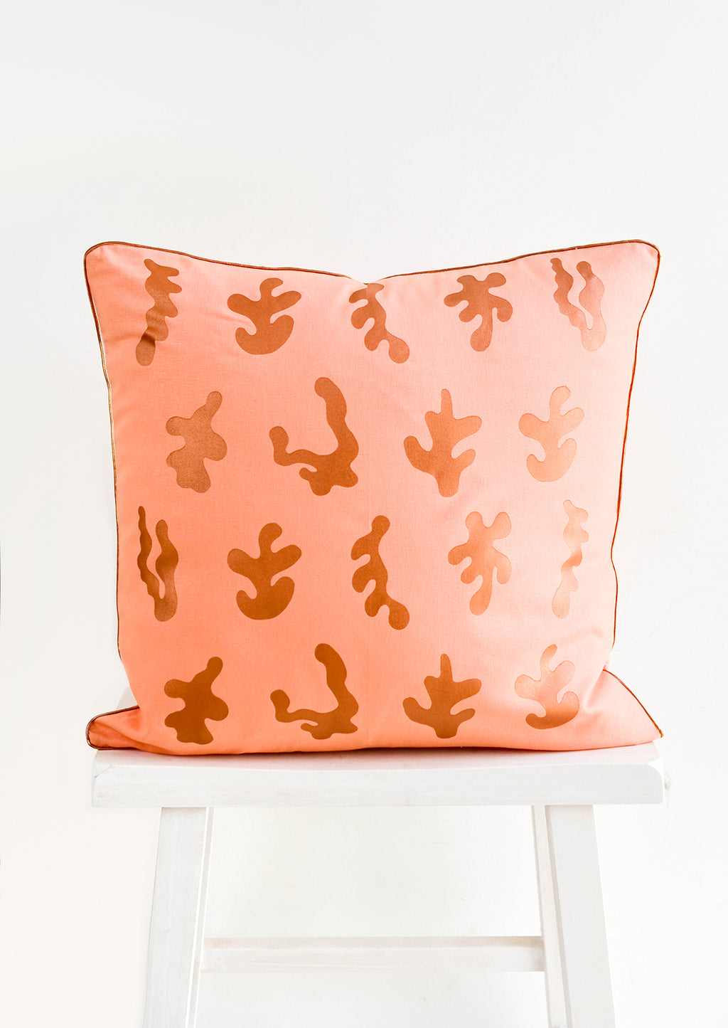 1: Square throw pillow in peach color with copper, screen printed seaweed shapes and copper trim
