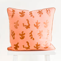 2: Square throw pillow in peach color with copper, screen printed seaweed shapes and copper trim