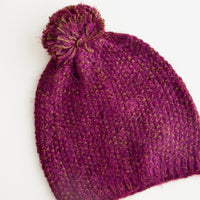 Aubergine: Purple knit beanie with pom pom on top.