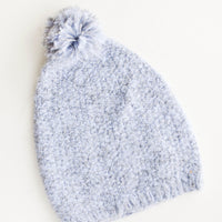 Cloud: Pale blue and gray knit beanie with pom pom on top.