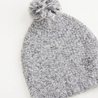 Ash: Gray knit beanie with pom pom on top.