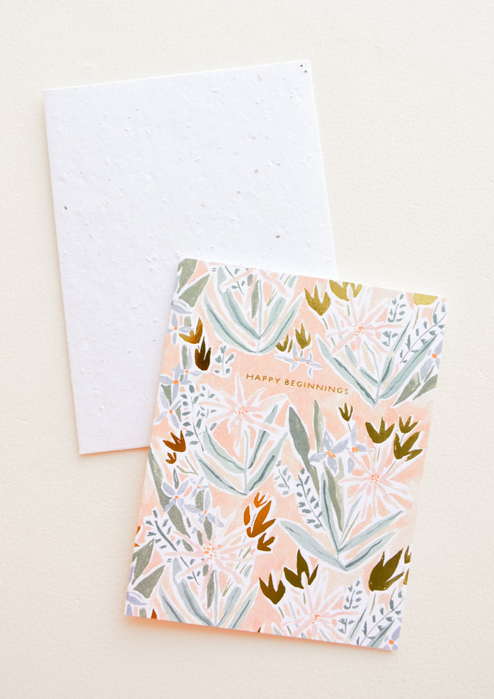 "1: Greeting card in peach color with floral print and ""Happy Beginnings"" text"