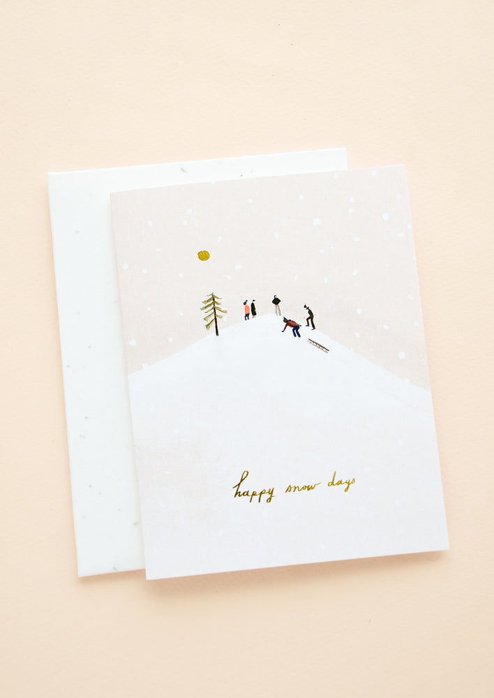 "1: Greeting card with image of people on a sledding hill, gold script at bottom reads ""Happy snow days"""