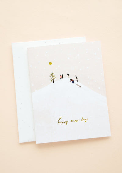 "Greeting card with image of people on a sledding hill, gold script at bottom reads ""Happy snow days"""