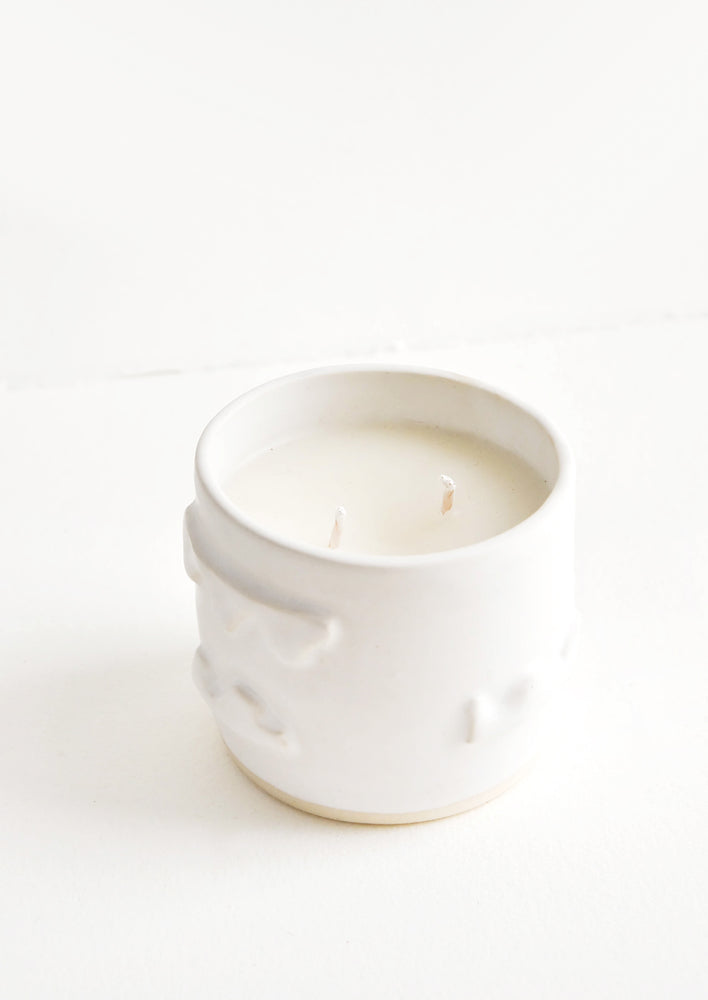 A candle in a white ceramic container affixed with three dimensional squiggles.