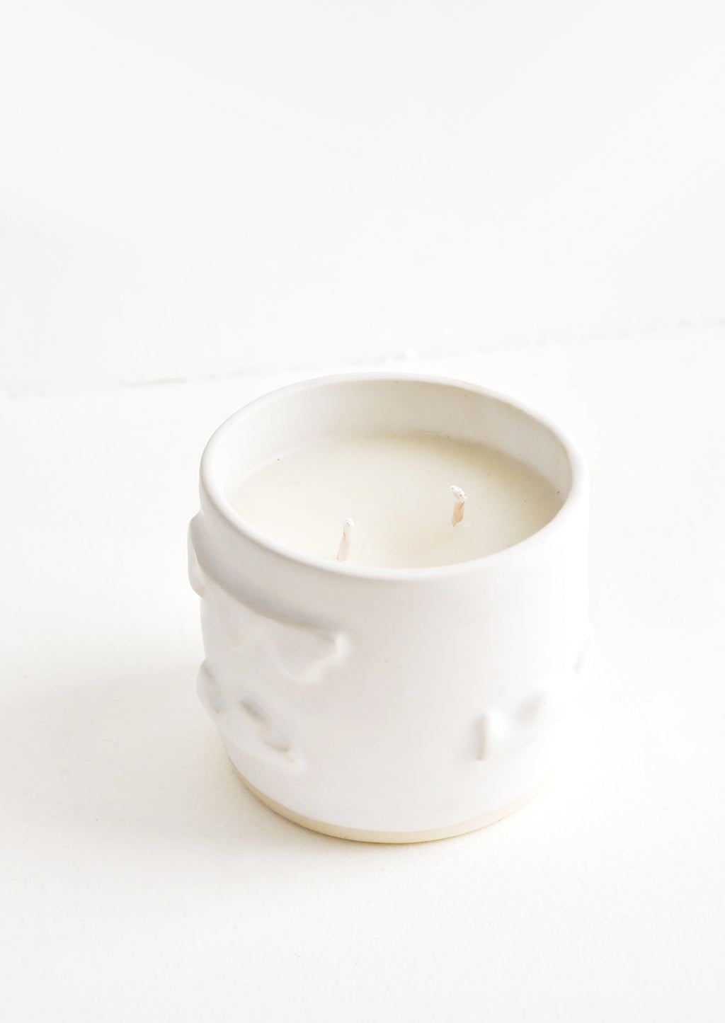 Arboretum: A candle in a white ceramic container affixed with three dimensional squiggles.