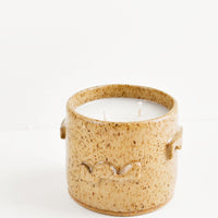 Santal: A candle in a light brown speckled ceramic container featuring three dimensional squiggles on its surface.