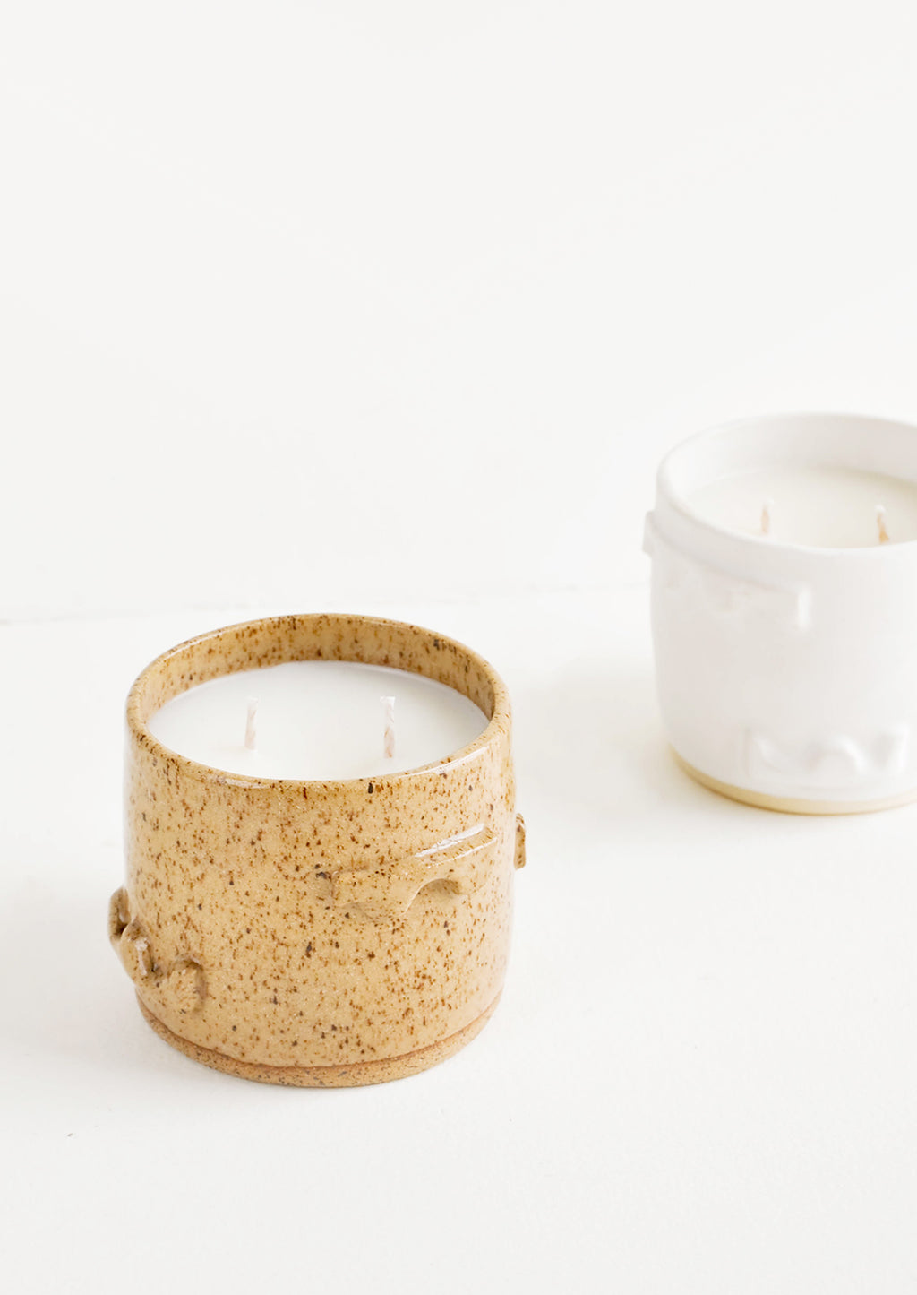 1: A candle in a light brown ceramic container with one in a white ceramic container just behind.