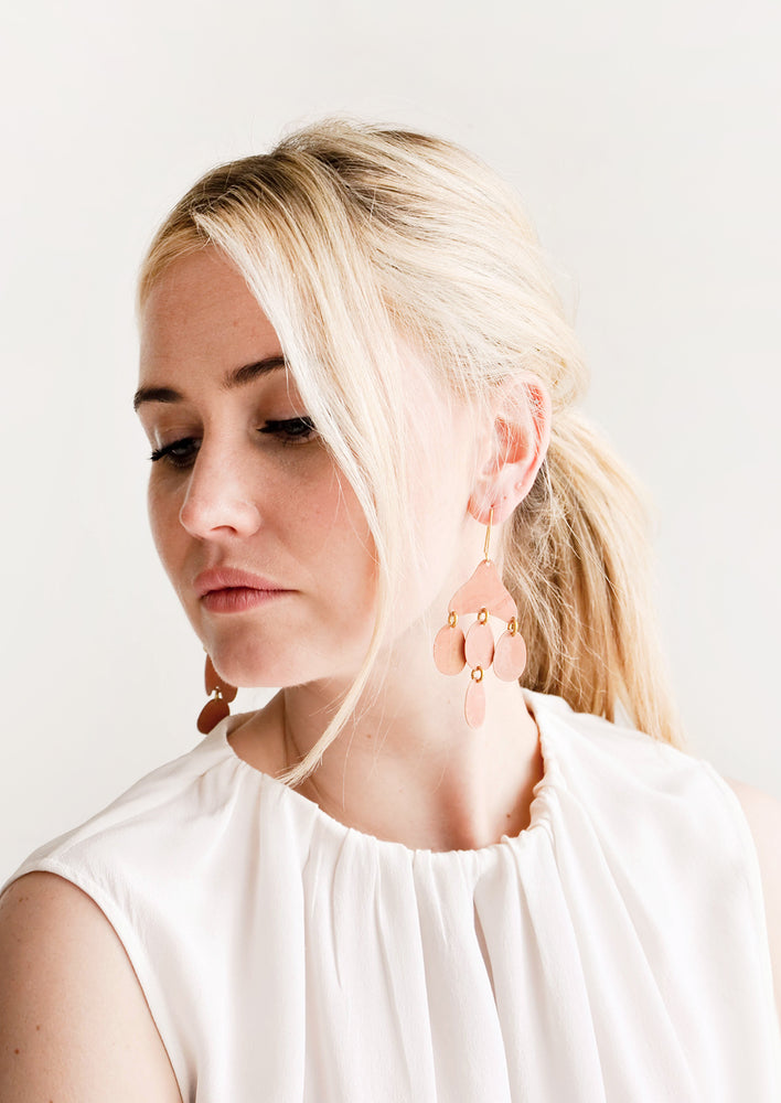 2: Model shot showing woman wearing earrings and a white top.