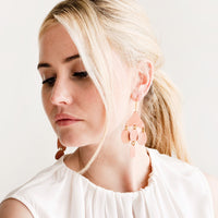 4: Model shot showing woman wearing earrings and a white top.