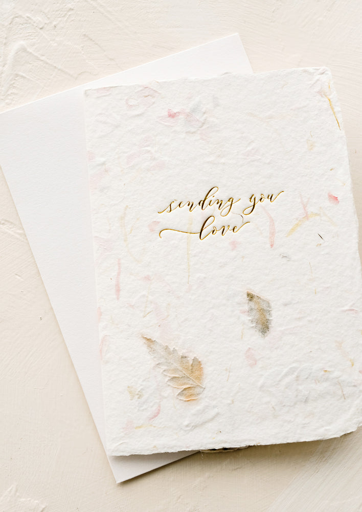 "1: A greeting card made from handmade flower paper with gold script on front that reads ""Sending You Love""."