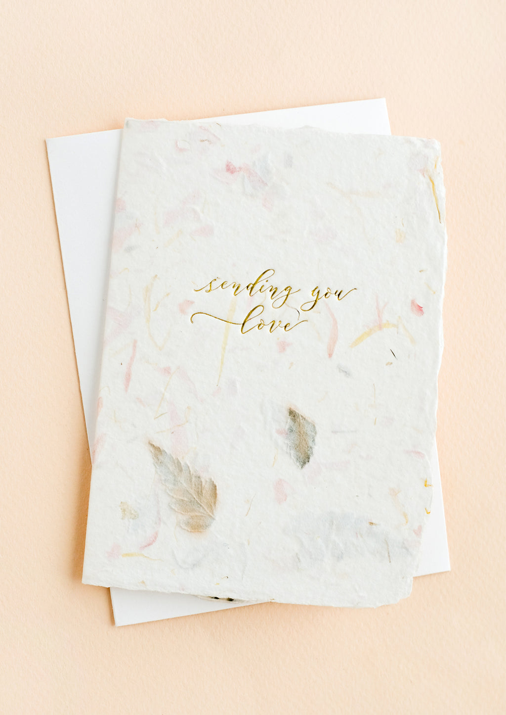 "3: A greeting card made from handmade flower paper with gold script on front that reads ""Sending You Love""."