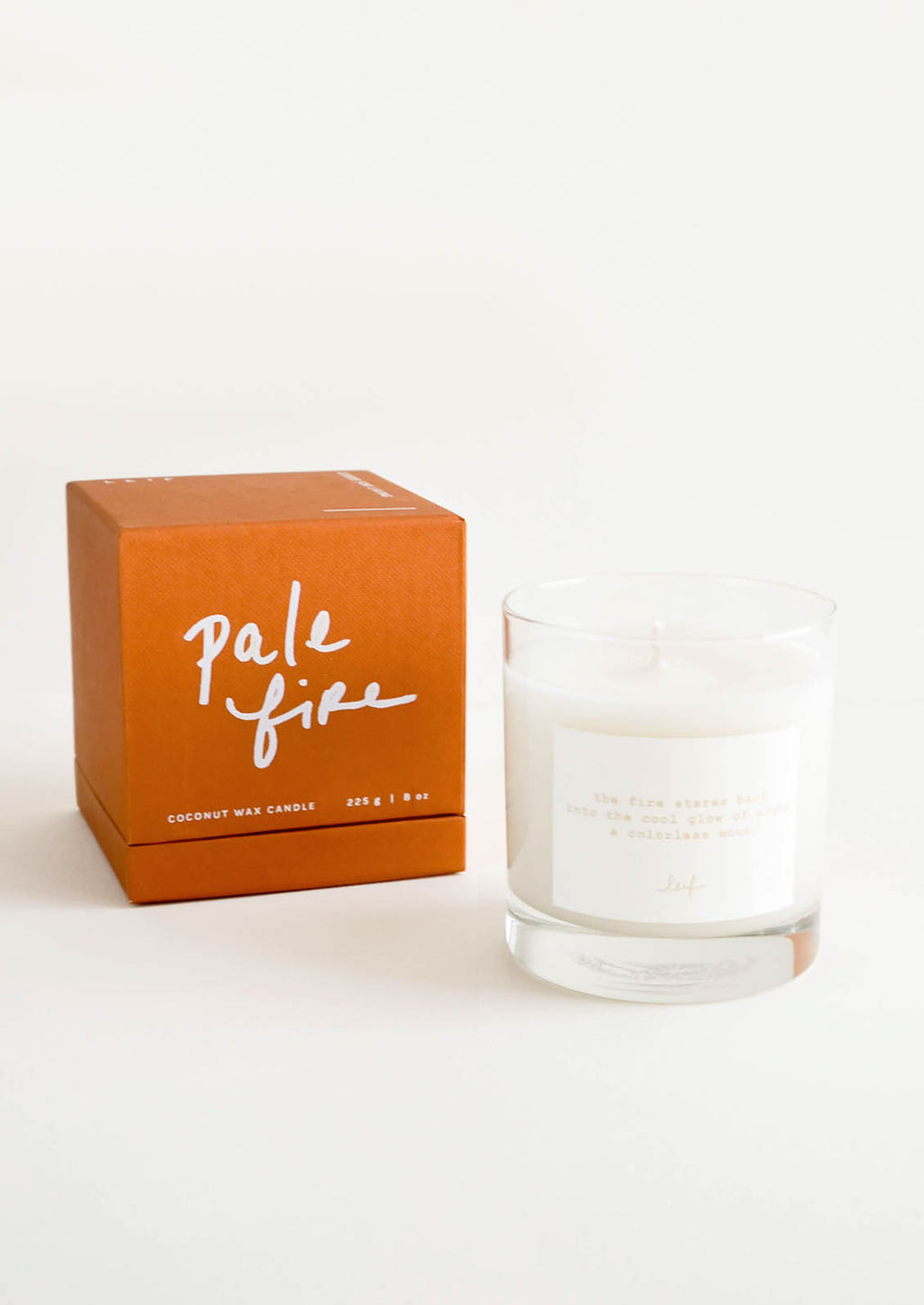 "Pale Fire: A glass candle with a white label sits next to a rust colored box reading ""pale fire"" in white cursive text."