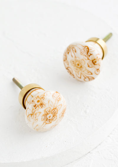 Two white ceramic knobs with sepia floral design and brass accents.