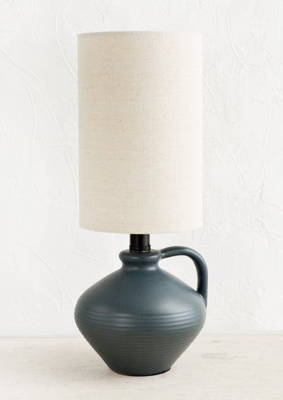 A table lamp with charcoal ceramic base and cylindrical natural cotton shade.