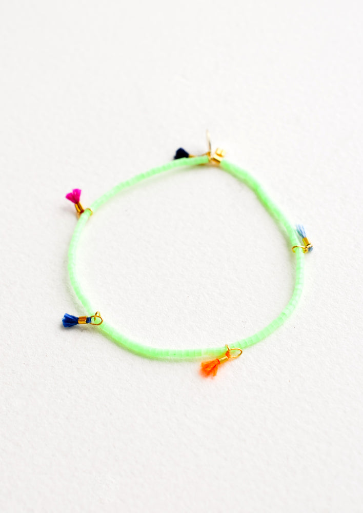 Mint Chip: Bracelet featuring green beads interspersed with 5 small multicolor string tassels on an elastic cord.