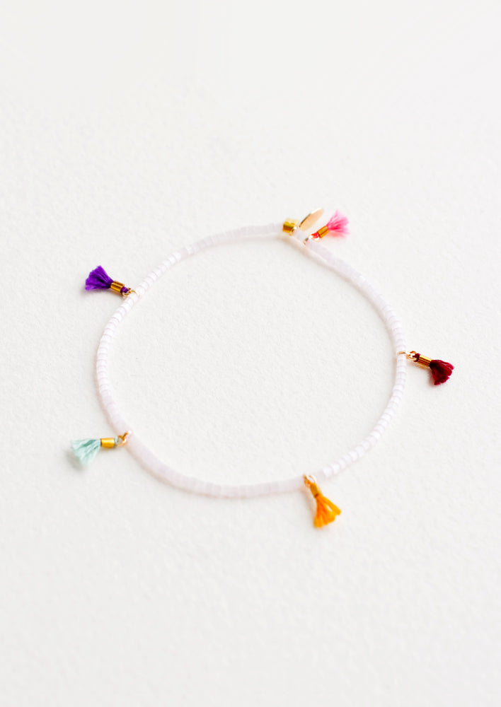 Rose Ice: Bracelet featuring white beads interspersed with 5 small multicolor string tassels on an elastic cord.