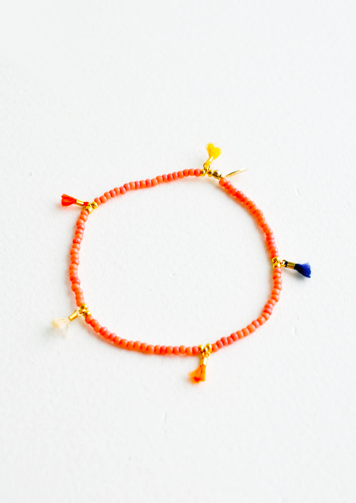 Red Coral: Bracelet featuring red beads interspersed with 5 small multicolor string tassels on an elastic cord.
