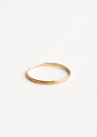 Slim yellow gold ring with textured surface.