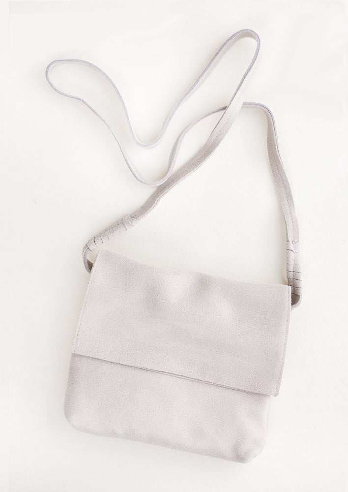 Putty: Pale gray soft leather bag with cross body strap and metallic sheen.
