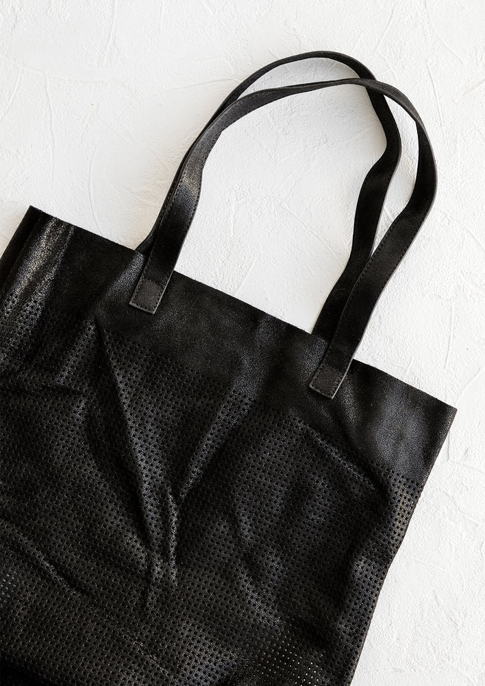 Black: A tote bag made from black colored shimmer leather with square perforation detailing throughout.