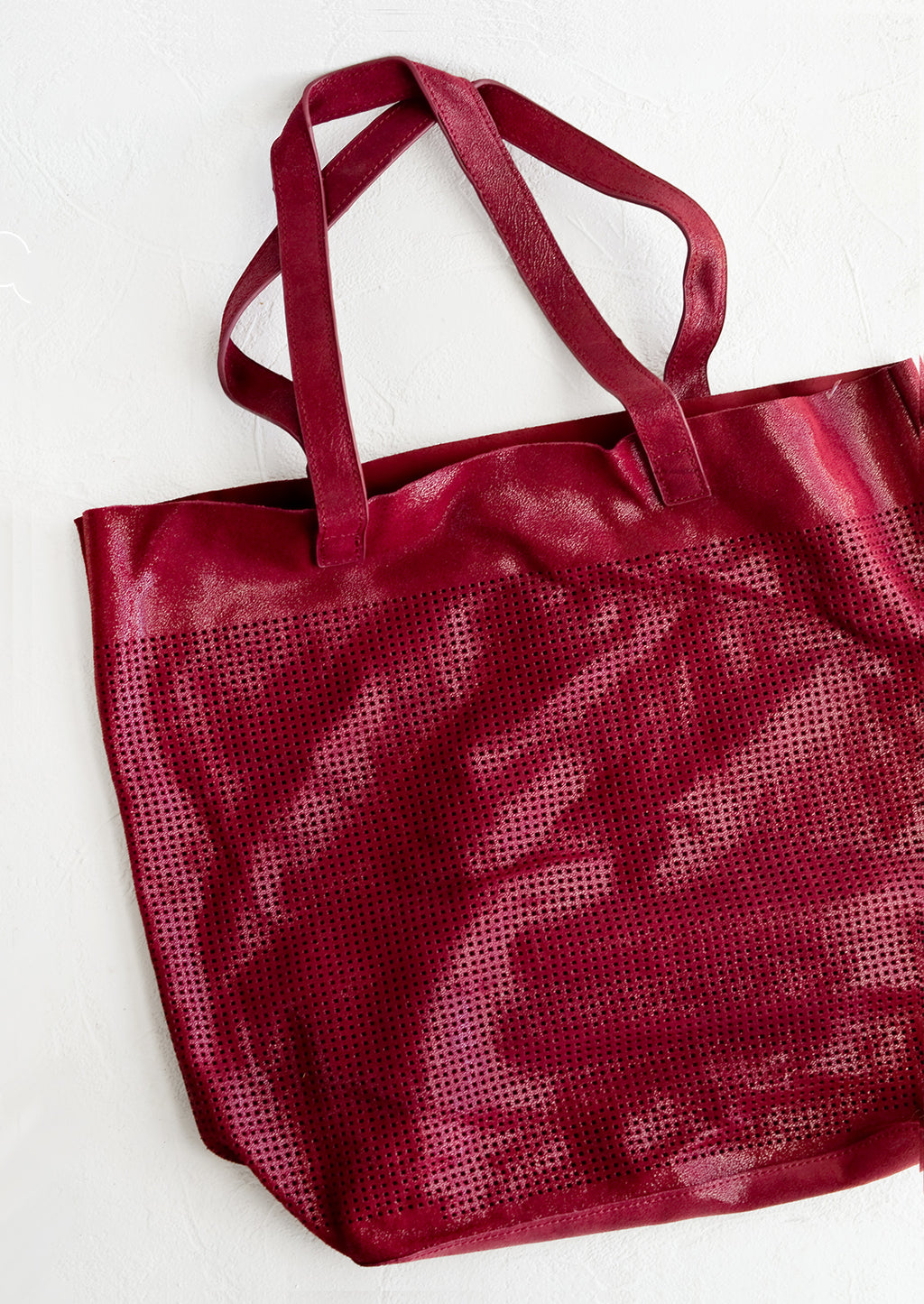 Cranberry: A tote bag made from cranberry colored shimmer leather with square perforation detailing throughout.