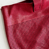 3: Perforation detailing on leather tote bag.