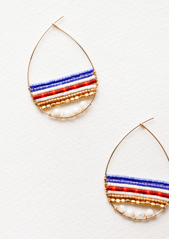 Teardrop shaped hoop earrings in yellow gold with multicolored beaded bars across.