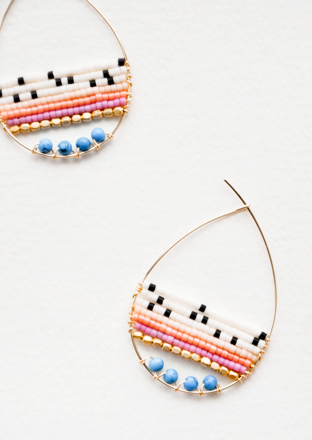 Ivory / Turquoise Multi: Teardrop shaped hoop earrings in yellow gold with multicolored ivory and turquoise beaded bars across.
