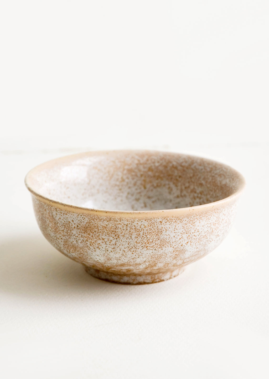 2: Small ceramic bowl with footed silhouette in reactive brown glaze