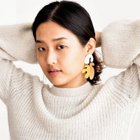 2: Model shot of woman wearing earrings and white sweater.