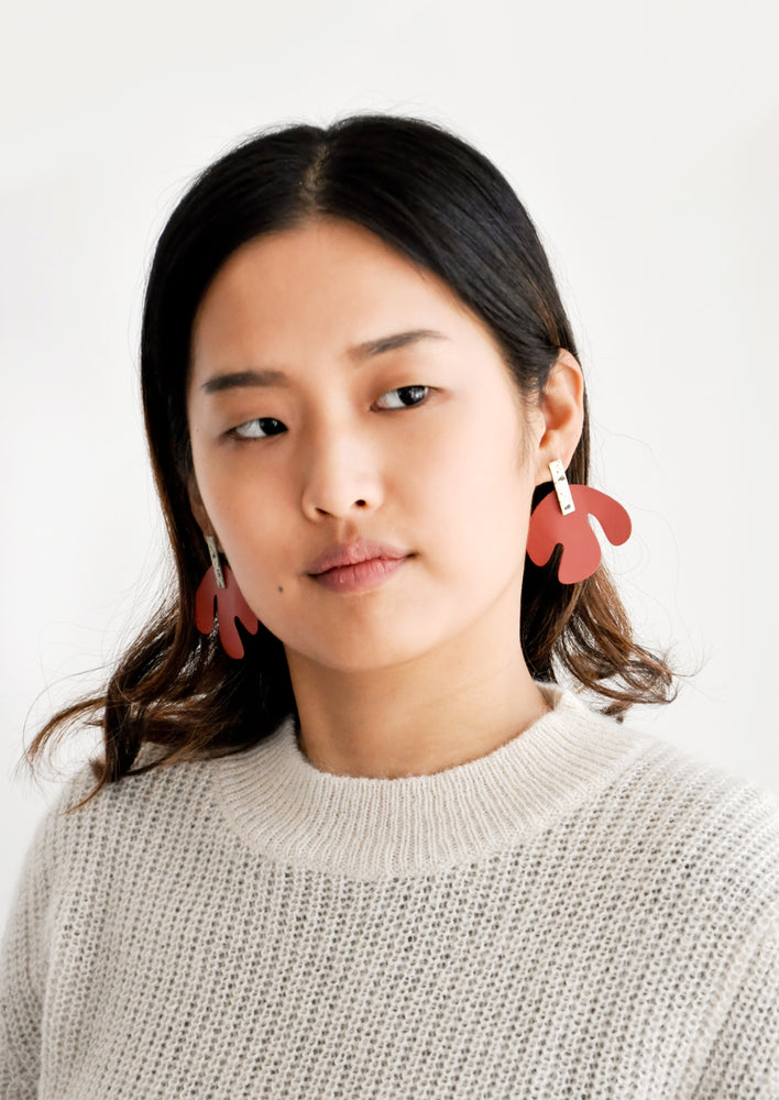 2: Model shot wearing earrings and a white sweater.