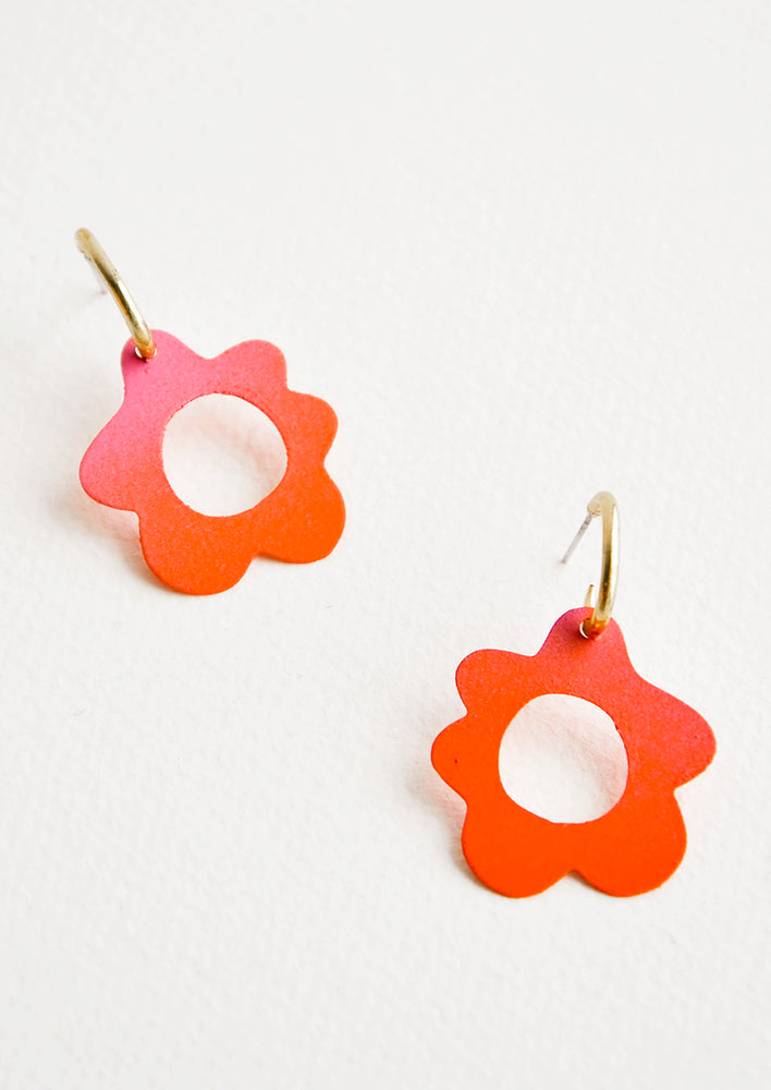 Coral flower shaped earrings with circular cutouts on small brass open hoops.