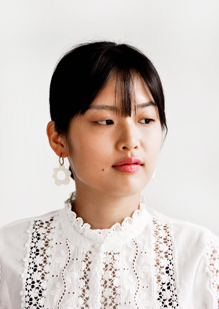 2: Model wears white flower-shaped earrings and white blouse.