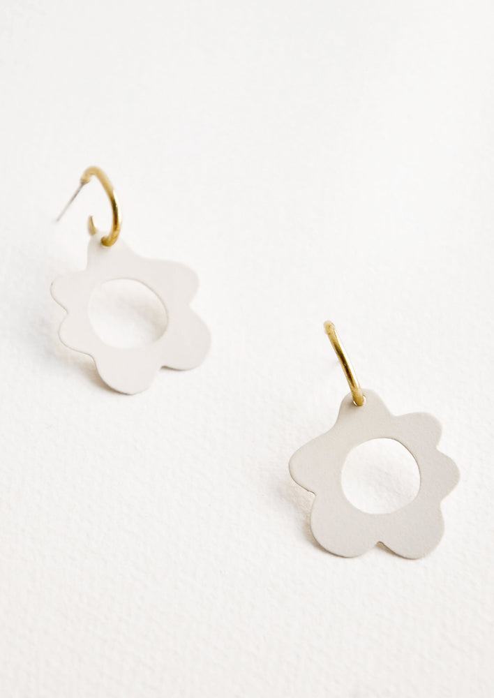 Cream: White flower shaped earrings with circular cutouts on small brass open hoops.