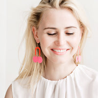 2: Model wears pink earrings and white blouse.