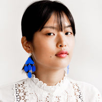 3: Model shot showing woman wearing earrings and a white top.