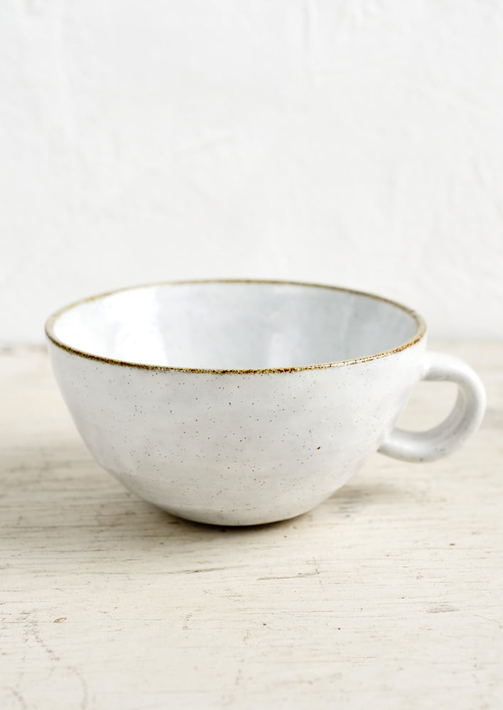 A ceramic latte mug in a glossy white glaze with soft speckles.