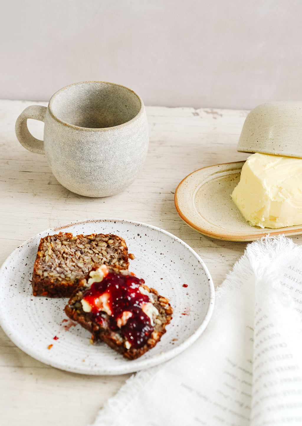 2: A breakfast tableware scene with coffee mug, butter dish and toast and jam on a ceramic plate.