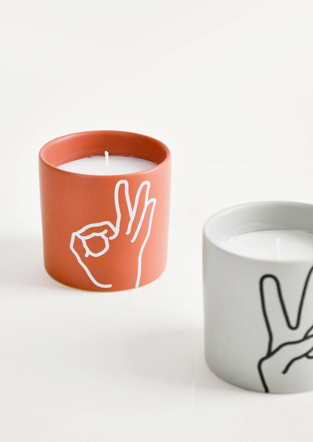2: Scented candles in colored ceramic jar with hand symbol graphics