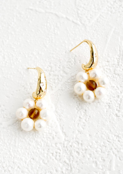 A pair of earrings with a crystal studded half-hoop top, and a flower shape made out of pearls.