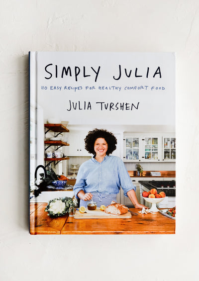 A hardcover cookbook with a woman in a kitchen on the cover.