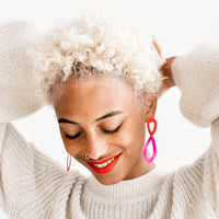 2: Model wears vibrant coral and fuchsia drop earrings and ivory sweater.