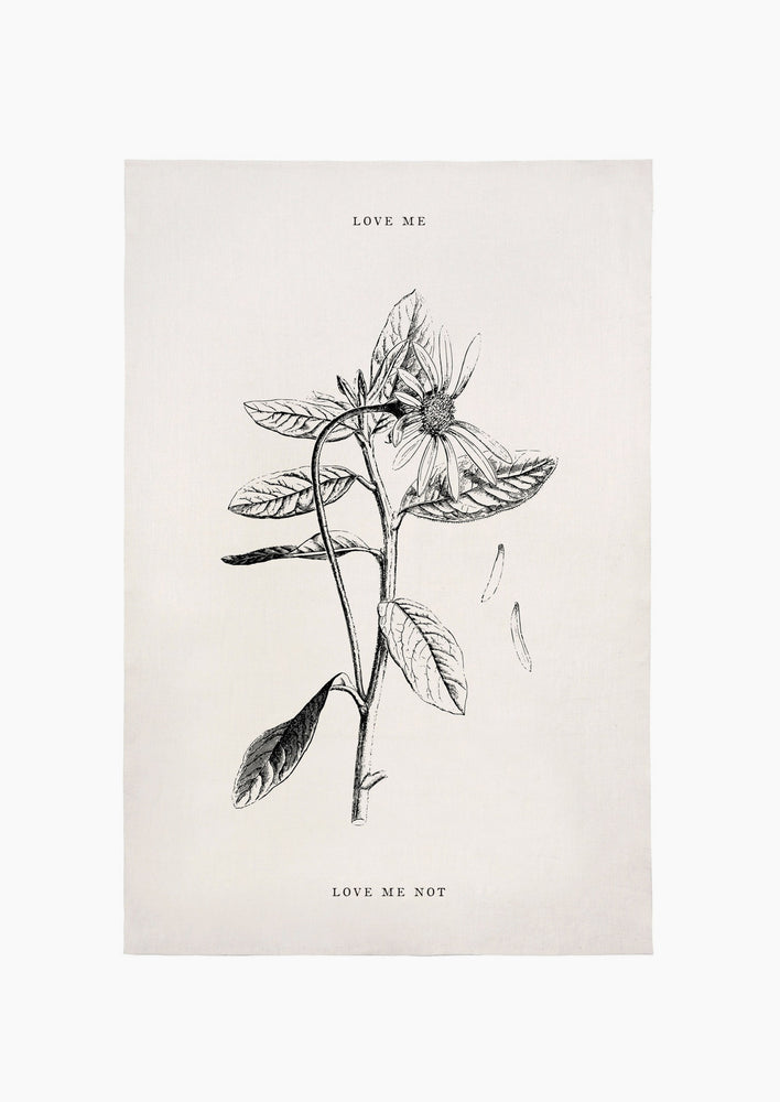 "1: A white linen tea towel with floral image and text reading ""love me"" and ""love me not""."