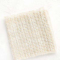 2: A folded washcloth made from natural sisal with a hanging loop at one corner.