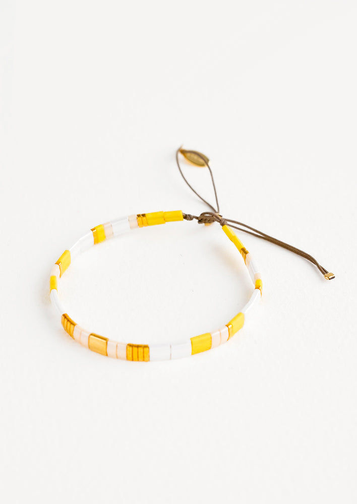 Yellow: Bracelet featuring flat yellow and white glass beads interspersed with flat gold bead on an adjustable cord.