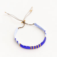 Blue: Bracelet featuring flat multicolor blue glass beads interspersed with flat gold bead on an adjustable cord.