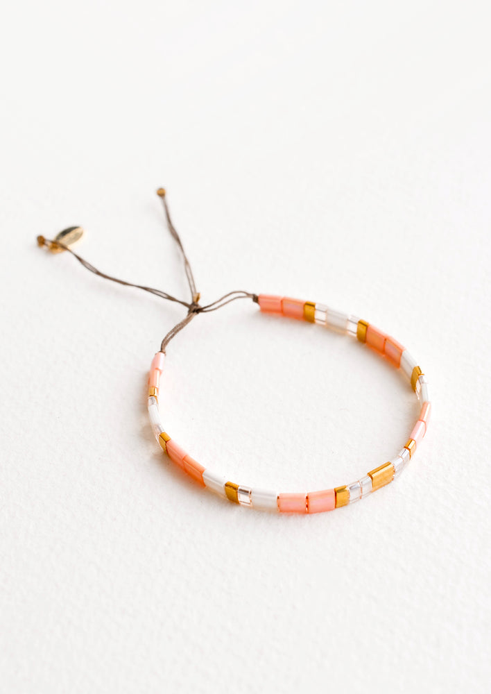 Bracelet featuring flat peach and white glass beads interspersed with flat gold bead on an adjustable cord.