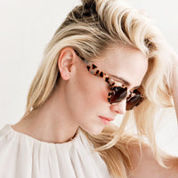 2: Model shot showing woman wearing sunglasses and white top.